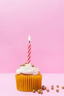 ピンクの背景のキャンドルで誕生日ケーキ