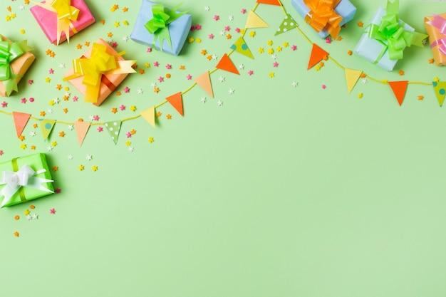 Плоские лежали красочные подарки на столе с зеленым фоном