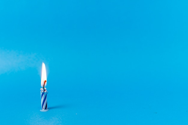 青色の背景に点灯ろうそく