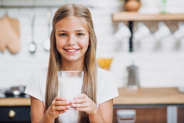 ミルクのガラスを保持しているスマイリーの女の子