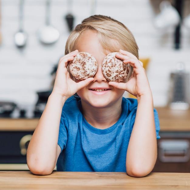クッキーで彼の目を覆っている小さな男の子