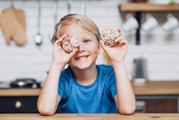 Маленький мальчик играет с печеньем