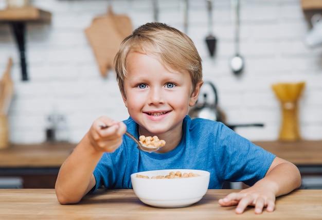 カメラを見ながら穀物を食べる少年