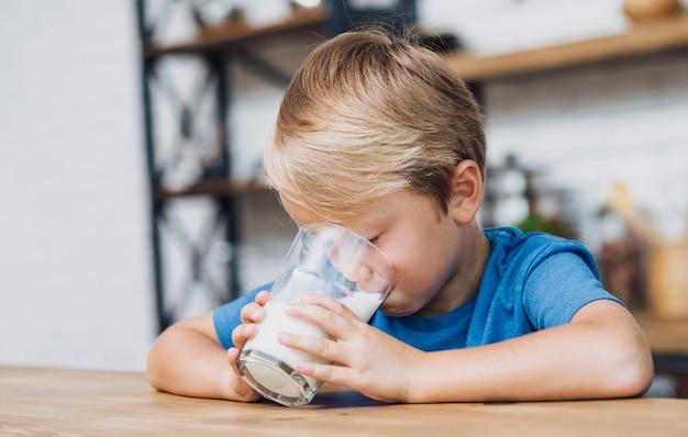 少しのミルクを飲む子供