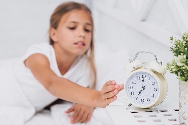 Маленькая девочка выключает будильник