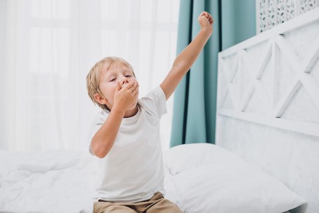 Маленький мальчик зевая после пробуждения