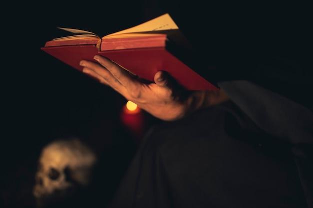Персона жестами держит красную книгу