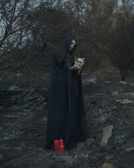 Человек стоит и держит череп для хэллоуина