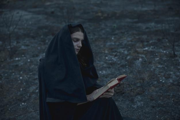 Человек читает книгу заклинаний снаружи