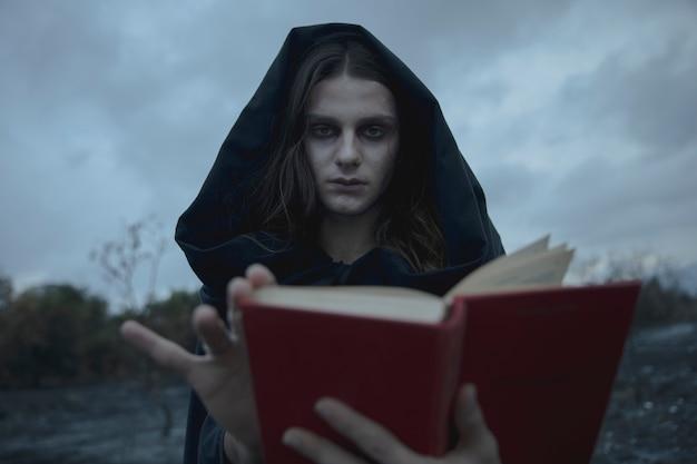 Человек с капюшоном, глядя на камеру с размытой книгой