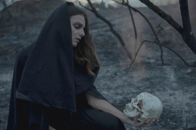 バックグラウンドで頭蓋骨と秋の枝を持つ黒のフード付きの男