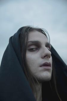 Крупным планом макияж ведьмы с черным капюшоном