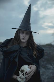 Ведьма мужчина держит реалистичный череп