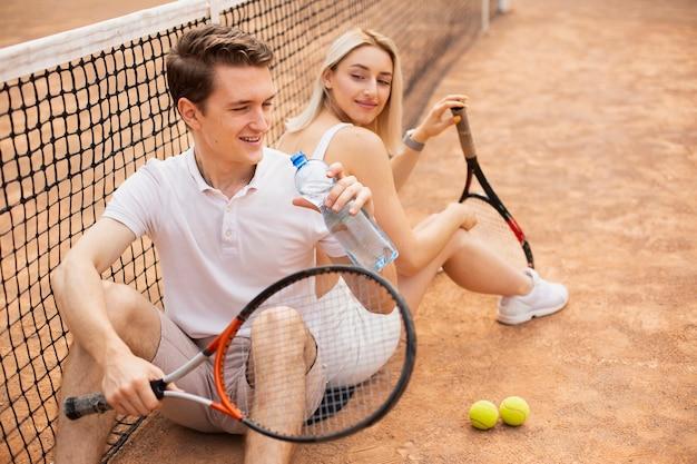 テニスコートでアクティブな若いカップル