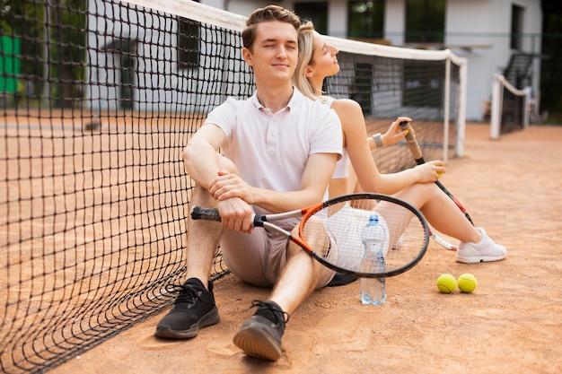 テニスコートで一緒に若いカップル