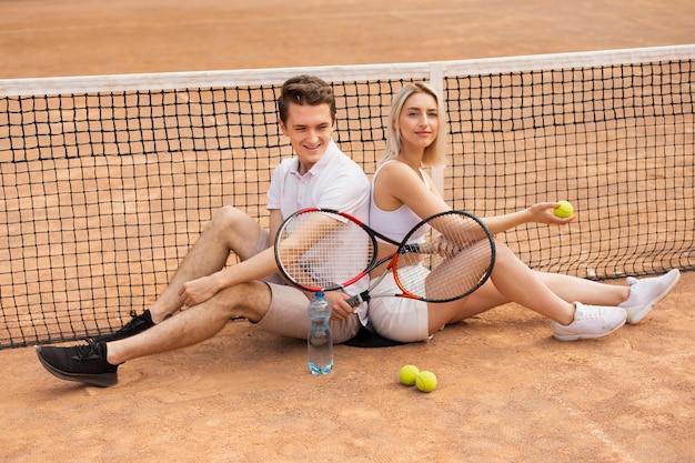 テニスコートの上に座ってフィットのカップル
