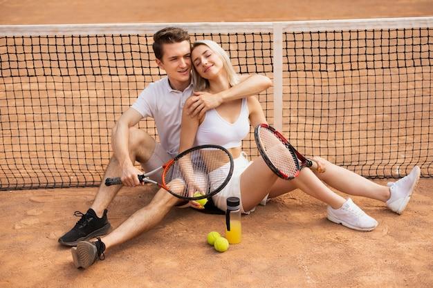 女性を抱き締めるテニスラケットを持つ男