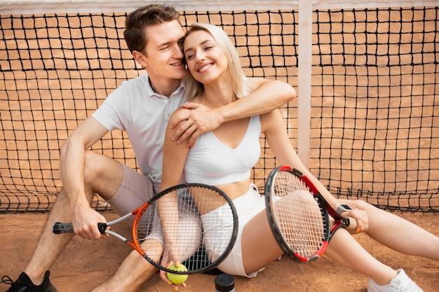 テニスコートで抱き締めるカップル
