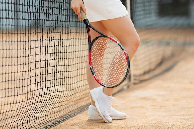Активная девушка стоит рядом с теннисной сеткой