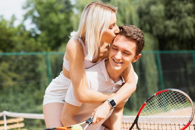 テニスコートで美しいアクティブなカップル