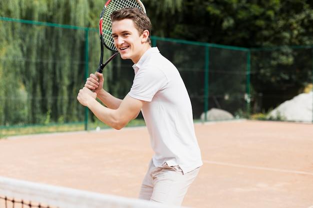 Активный молодой человек играет в теннис