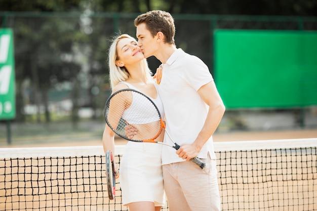 テニスコートで若いカップルに合う