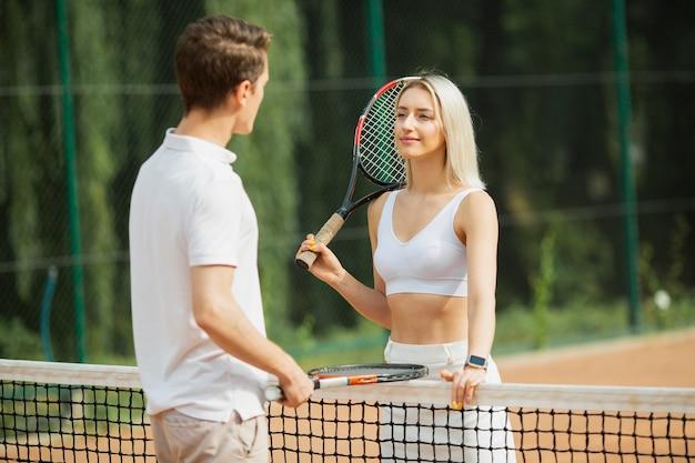 テニスネットの横にある若い男と女