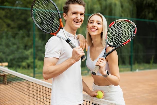 Теннисная пара с ракетками позирует