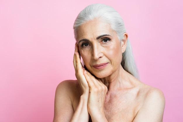 Уверенно старшая женщина с розовой предпосылкой
