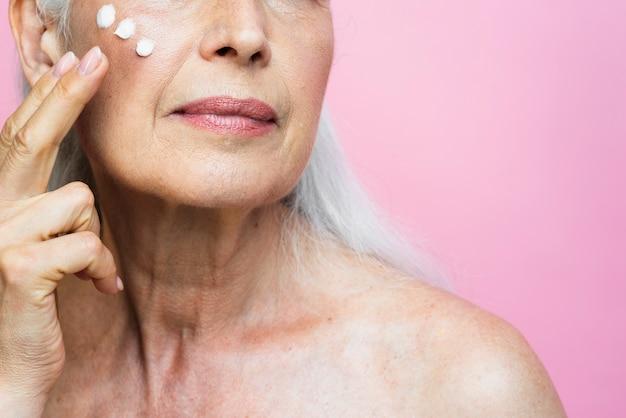 Крупным планом старшая женщина, применяя крем