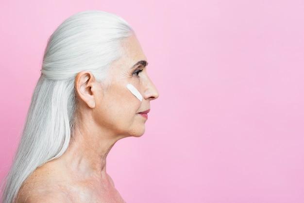 ピンクの背景を持つ美しい年配の女性