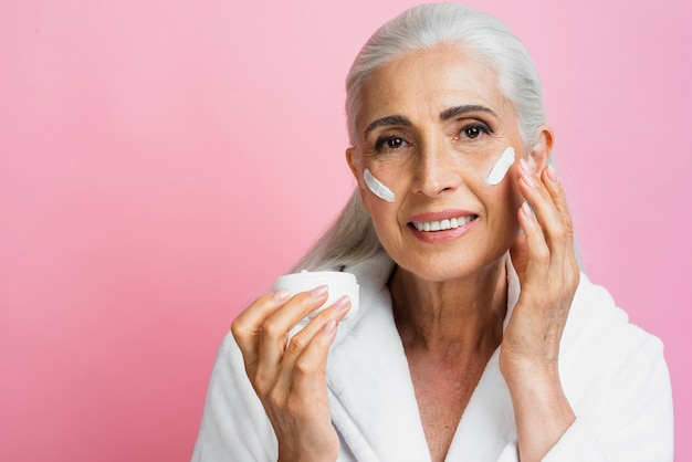 Вид спереди старшая женщина тестирование увлажняющего крема