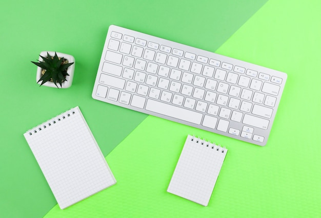 Расположение канцелярских принадлежностей сверху на зеленой предпосылке с пустыми блокнотами