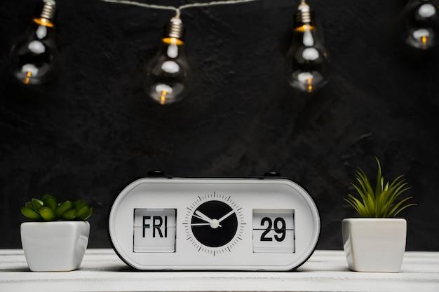 時計と木製のテーブルと電球の正面図