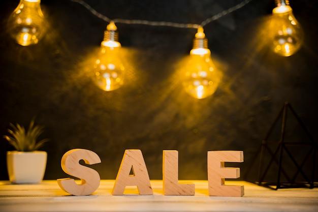 木製のテーブルと販売単語と電球の正面図