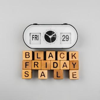 Взгляд сверху часов и кубиков продажи черной пятницы