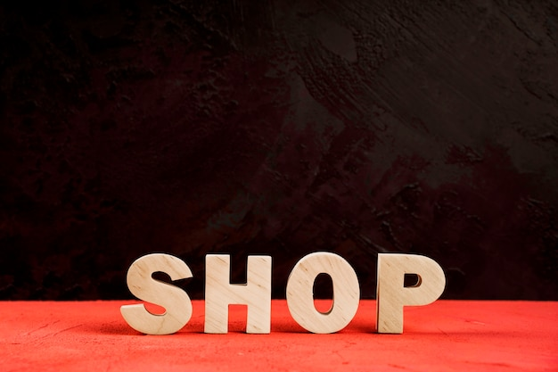 Вид спереди магазина слова на красном столе