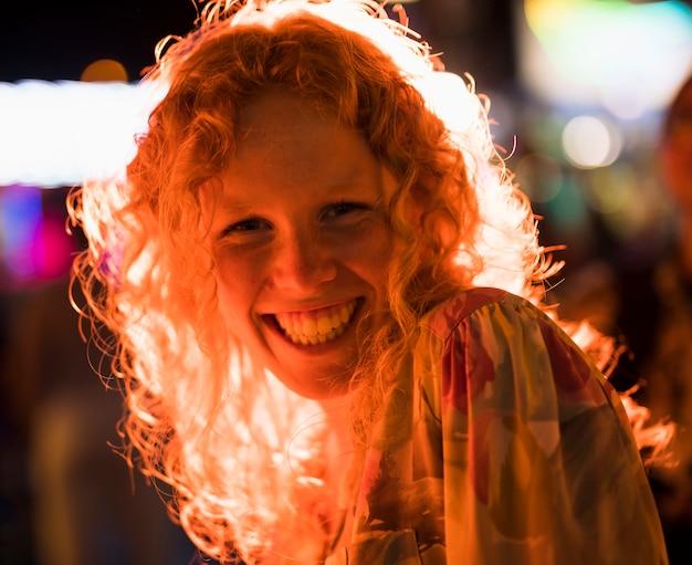 Радостная женщина улыбается, глядя на камеру