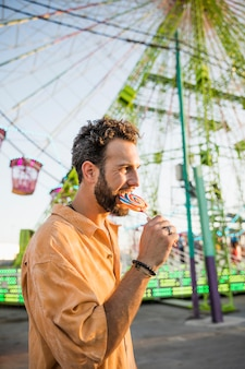 遊園地でロリポップを食べているハンサムな男