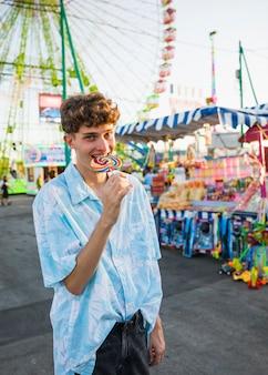 Детский человек, наслаждаясь леденец на ярмарке