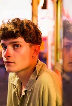 Молодой человек, глядя на камеру на ярмарке