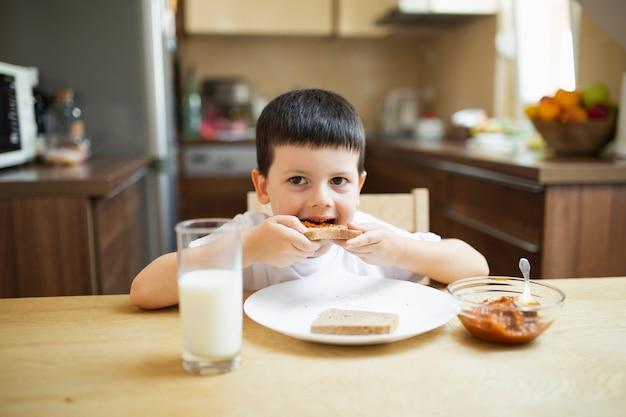 Мальчик завтракает дома