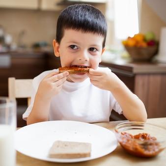 自宅で朝食を持っている男の子