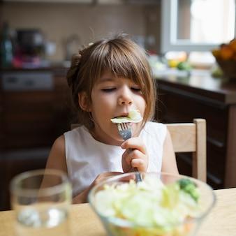 自宅で健康的な食事を持つ少女