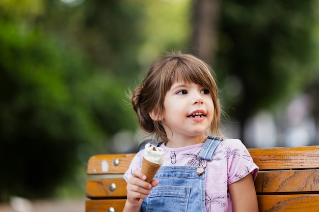 Девочка сидит на скамейке во время еды мороженого