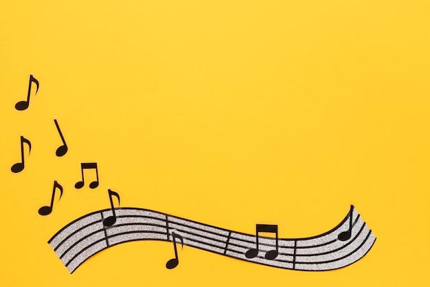 ミュージカルステーブと黄色の背景にノート