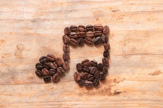 木製の背景にコーヒー豆から作られた音符