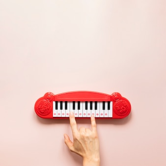 ピンクの背景に手とピアノのおもちゃ