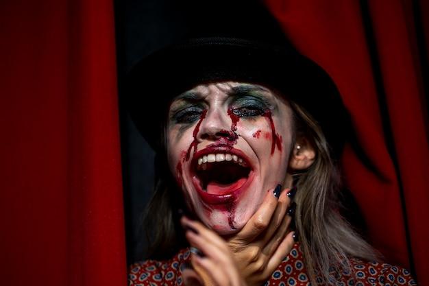 Женщина с макияжем, как кровь смеется