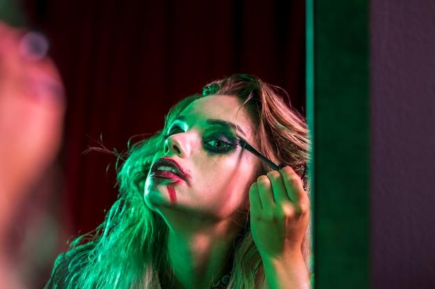 鏡で彼女の化粧を修正する女性